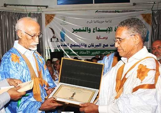 الإديب والإعلامي محمد كابر هاشم في يسار الصورة يستلم التكريم من الناطق الرسمي باسم الحكومة الموريتانية (وم أ)