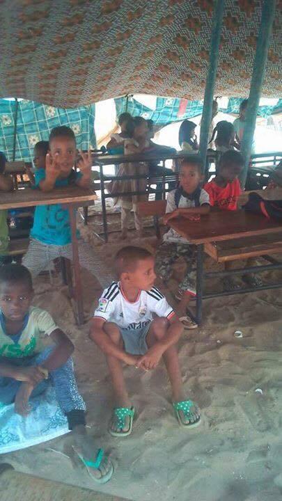 بعض الطلاب على المقعد وآخر على الأرض تحت الخيمة