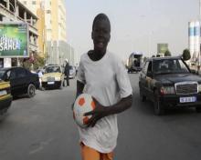 الطفل آمدو بطل الفلم وهو يركض حاملا الكرة بين يديه (لقطة من الفلم) - (السراج)