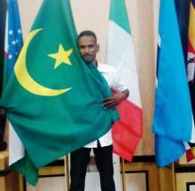 صورة للبطل الموريتاني في لعبة الشطرنج سيدي ولد بيديا وهو يحمل العلم الموريتاني(السراج)