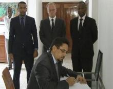 الوزير الناطق باسم الحكومة أثناء توقيعه في سجل التعازي بالسفارة الألمانية (وم أ)