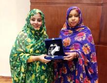 الموريتانيتان المنتدبتان من وزارة الشؤون الاجتماعية والطفولة والأسرة وهما يحملان تكريما للمرأة الموريتانية (السراج)